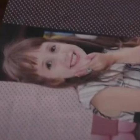 Mãe folheia álbum de fotos da vítima Isabele, morta aos 14 anos com um tiro na cabeça - Reprodução/TV Globo