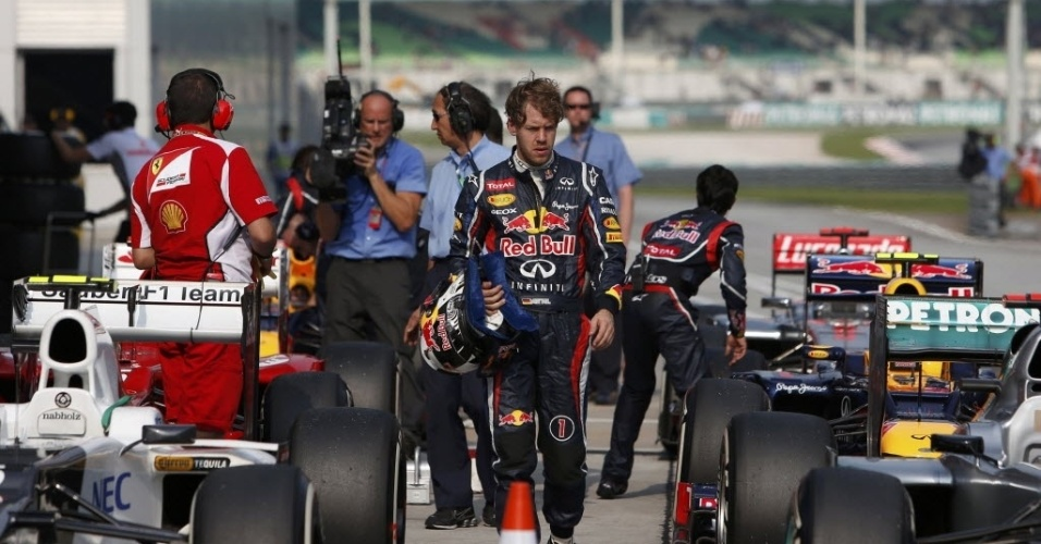De cara feia, quinto colocado Sebastian Vettel passa pelos carros estacionados após o treino oficial da Malásia