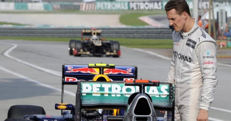 Michael Schumacher observa carros estacionados após fazer o terceiro melhor tempo no treino oficial na Malásia