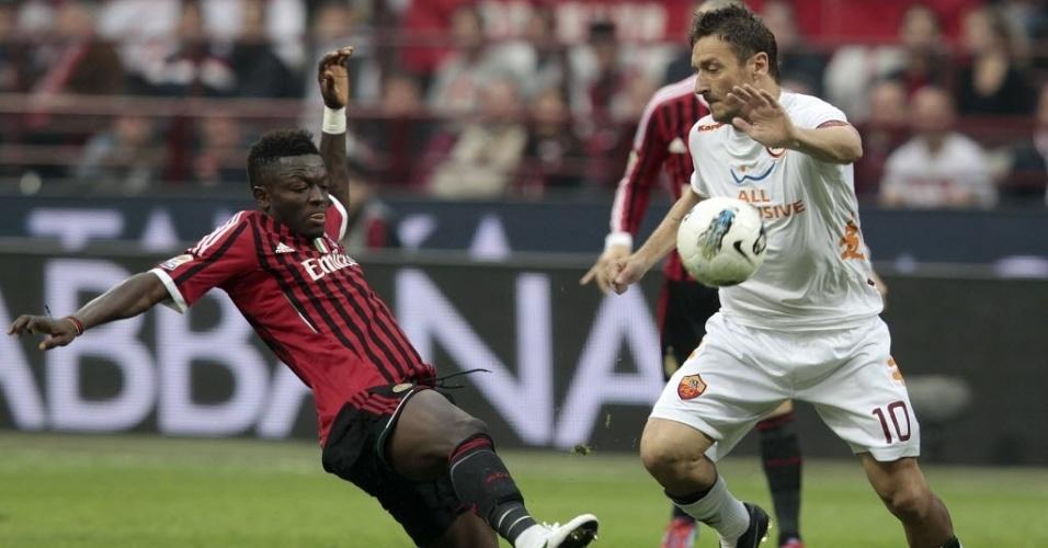 O capitão da Roma, Francesco Totti carrega a bola marcado pelo volante Muntari, do Milan