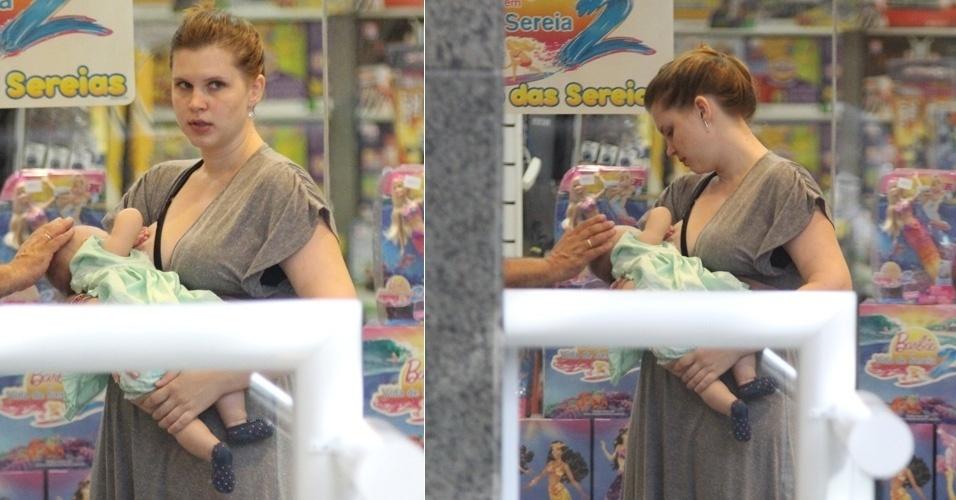 A atriz Carolinie Figueiredo amamenta a filha Bruna Luz durante passeio no shopping Rio Design Barra, no Rio de Janeiro (27/3/12)