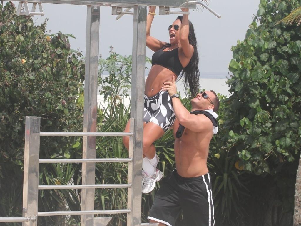 Ex-BBB Kelly recebe ajuda do namorado Fernando David para fazer exercícios na orla da praia da Barra da Tijuca (27/3/12)