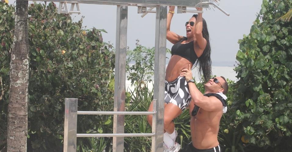 Ex-BBB Kelly recebe ajuda do namorado para fazer exercícios na orla da praia da Barra da Tijuca (27/3/12)