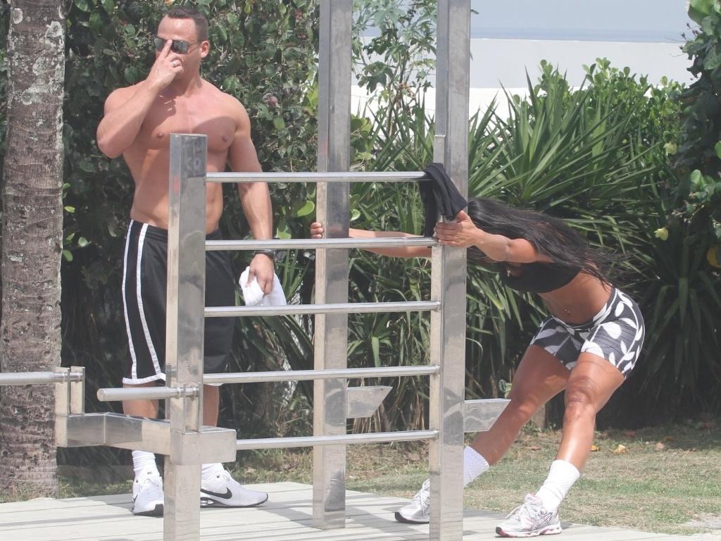 Ex-BBB Kelly se alonga depois de fazer exercícios na orla da praia da Barra da Tijuca com o namorado Fernando David (27/3/12)