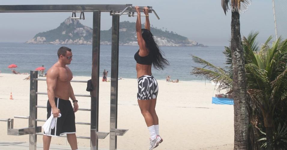 Ex-BBB Kelly se exercita na orla da praia da Tijuca enquanto é observada por Fernando, seu namorado (27/3/12)