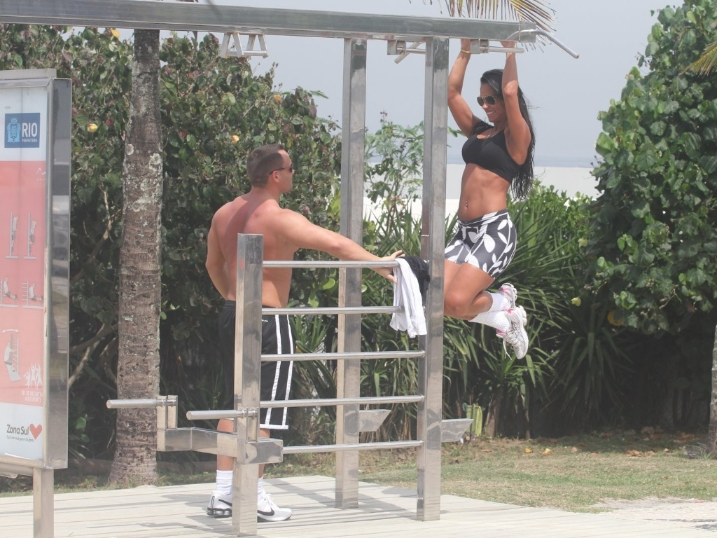 Observada pelo namorado Fernando, a ex-BBB Kelly faz exercícios na orla da praia da Barra da Tijuca (27/3/12)