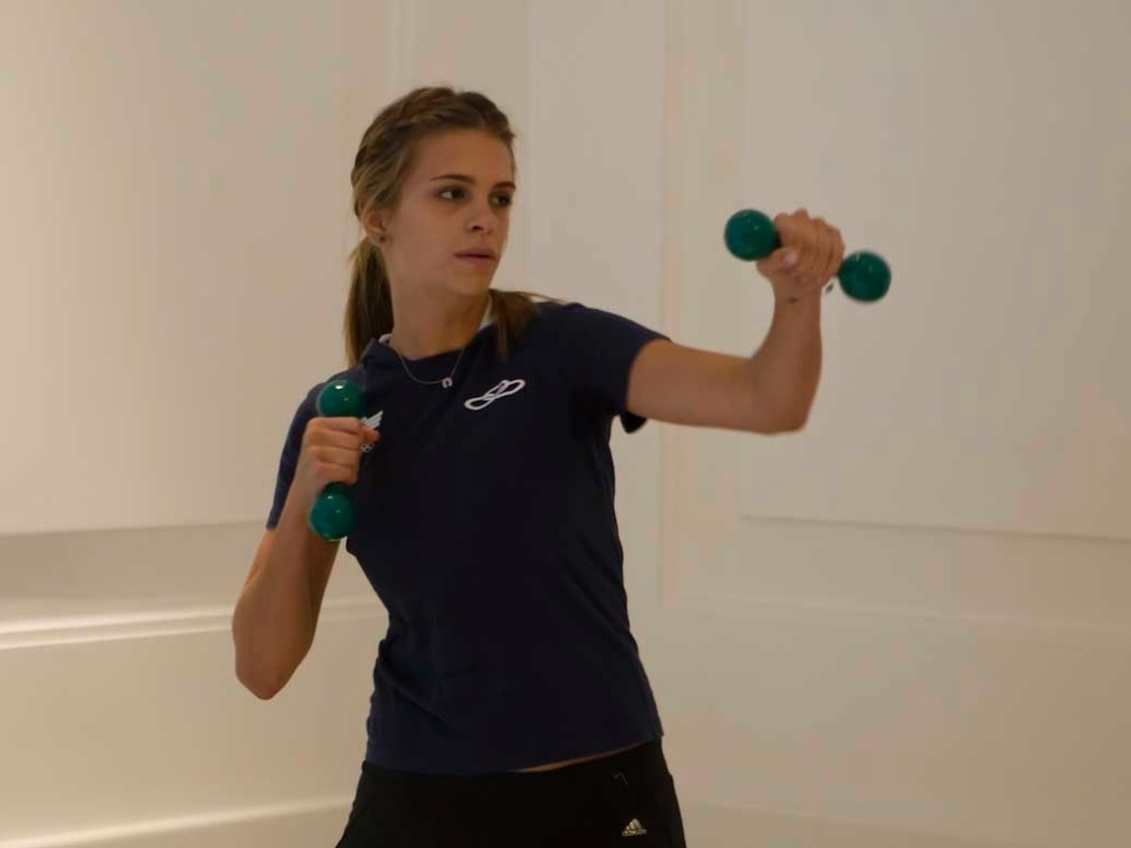 A amazona Luiza Almeida simula golpes de boxe com pesos de academia