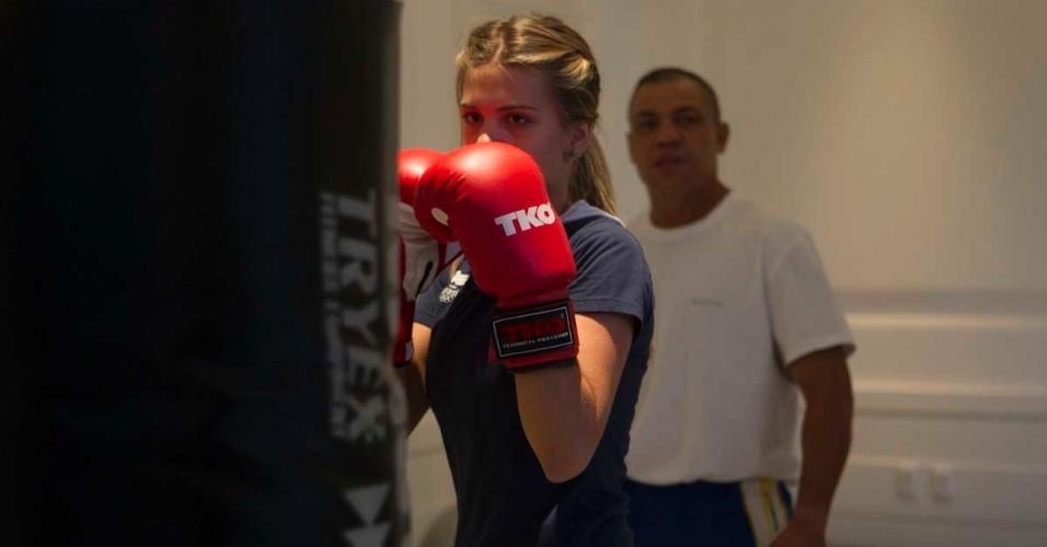 Devidamente trajada com a luvas, Luiza Almeida se prepara para acertar o saco de areia em seu treino de boxe