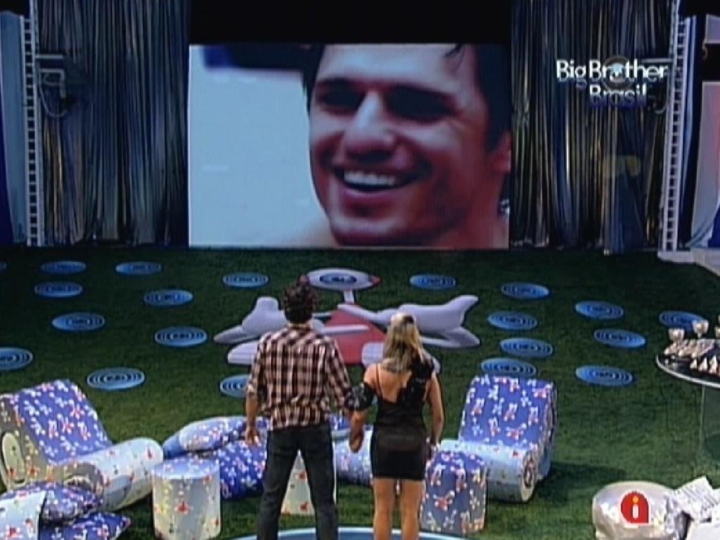 Fabiana e Fael olham imagem de João Maurício no telão da última festa do programa (28/3/12)