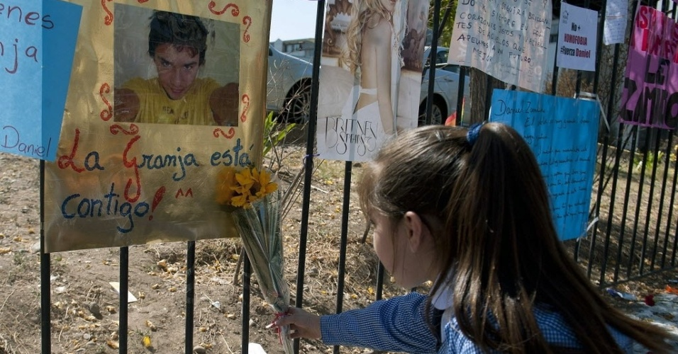 Garota coloca uma flor ao lado de mensagens de apoio ao chileno Daniel Zamudio em frente ao hospital público de Santiago. Zamudio, um homossexual de 24 anos atacado por neonazistas, morreu após 25 dias em coma