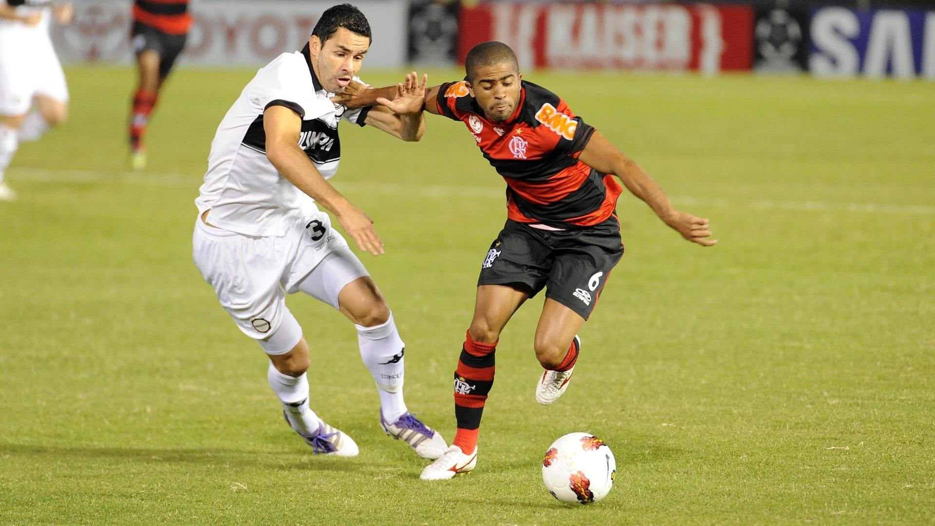 Júnior César encara a marcação na partida entre Olimpia e Flamengo (28/03/12)