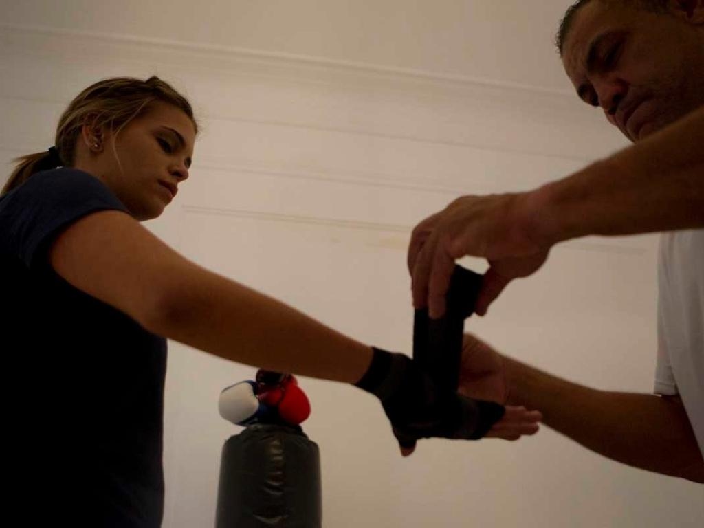 O treinador Jorge Mello ajeita as ataduras de Luiza Almeida antes do treino de boxe da atleta