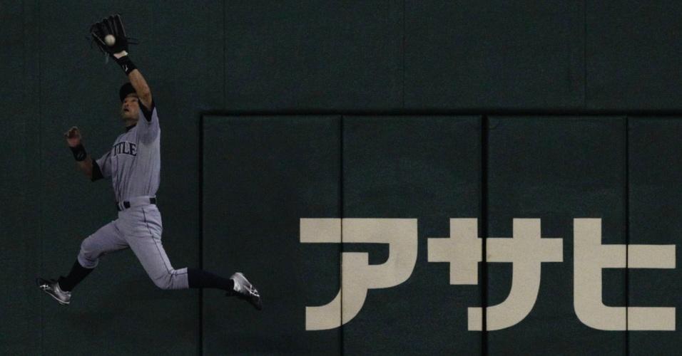 Jogador do Seattle Mariners pula para pegar a bola do Oakland Athletics Kurt Suzuki na liga americana MLB, em Tóquio