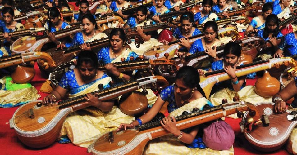"""Um grupo de 1.110 mulheres interpretam pela primeira vez a """"Sinfonia Musical"""" com veenas --instrumento musical indiano de sete cordas--, durante concerto para bater o recorde mundial do maior número de mulheres tocando o instrumento no mundo, em Bangalore, na Índia"""