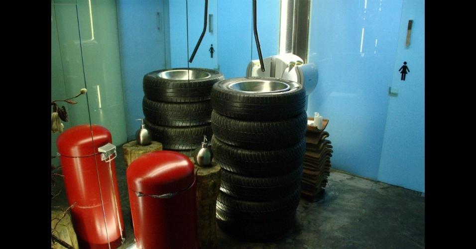 Detalhe do banheiro do gastrobar La Gabinoteca, cuja pia foi feita com pneus empilhados e a torneira é uma mangueira acionada por um pedal instalado no chão