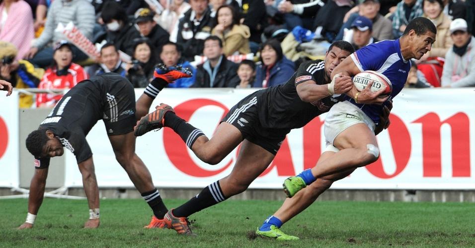 Afa Aiono, da seleção de rugby sevens de Samoa, passa pela defesa da Nova Zelândia em partida válida pelo torneio Sevens World Series, etapa de Tóquio, no Japão