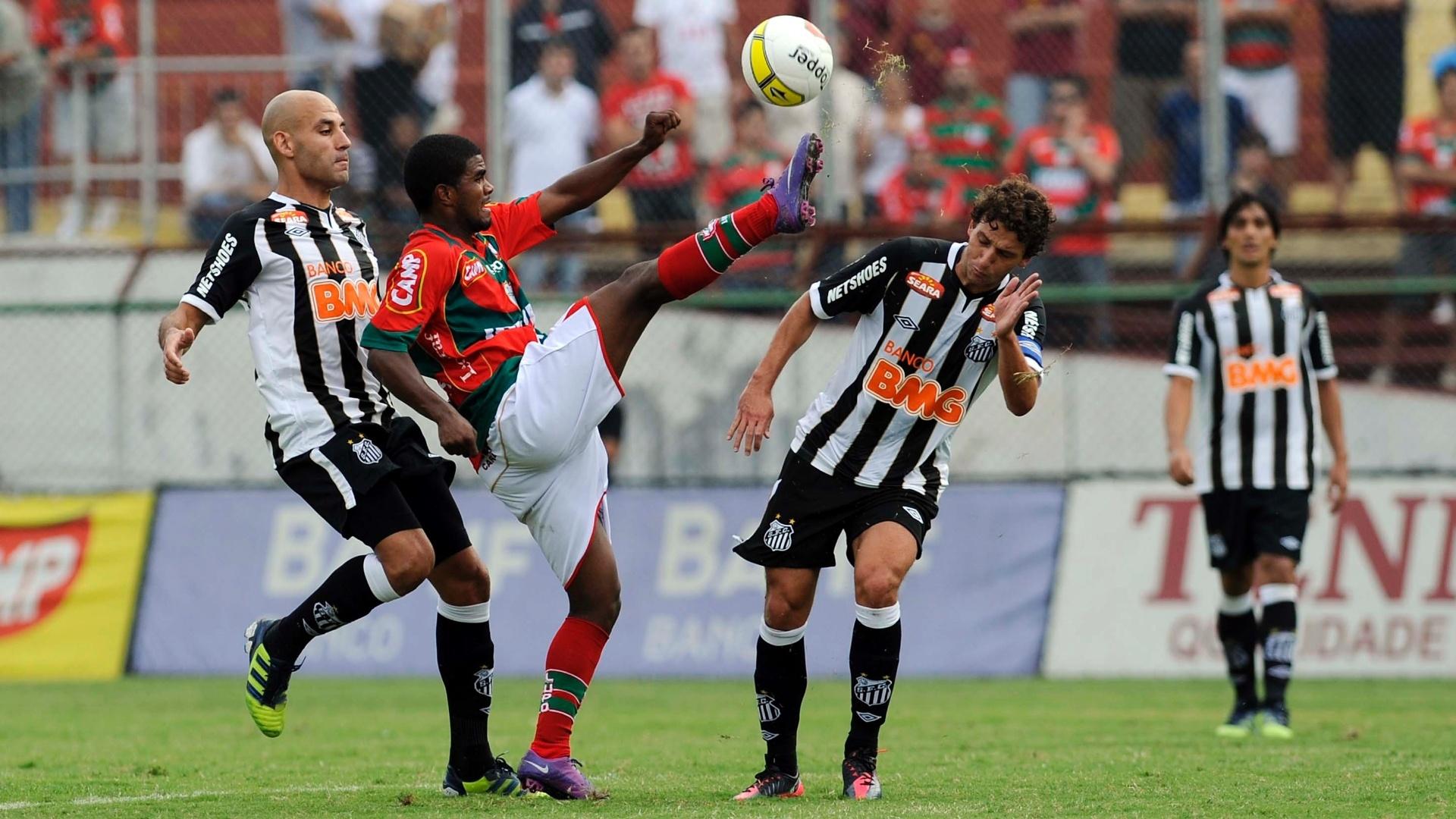 Henrique, da Portuguesa, tenta sair da marcação de Bruno Rodrigo (esq) e Elano, do Santos
