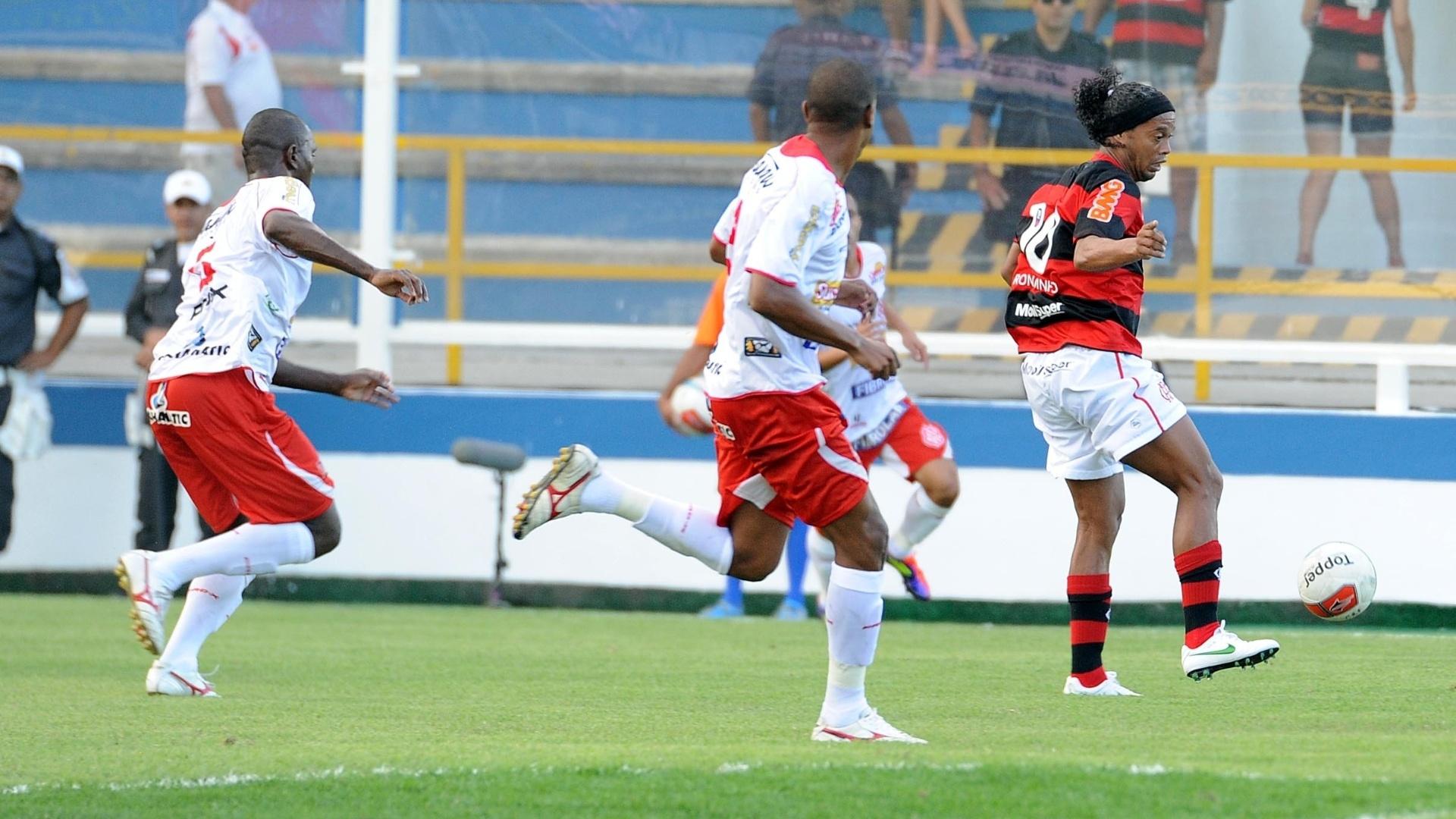 Ronaldinho Gaúcho domina a bola cercado por três marcadores do Bangu durante partida em Macaé