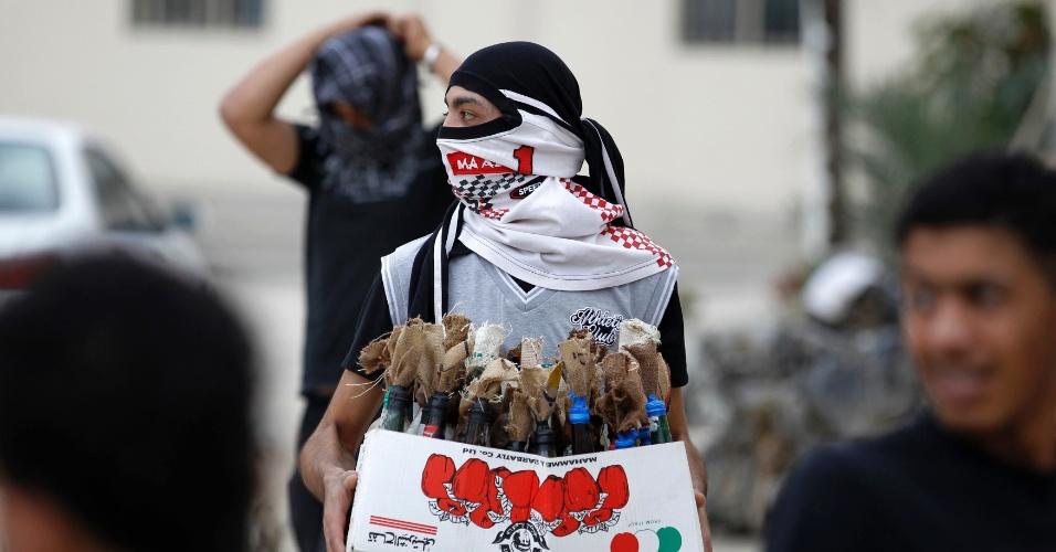 Bareinita carrega caixa com diversos coquetéis Molotov durante protestos no vilarejo de Salmabad, ao sul de Manama, capital do Bahrein