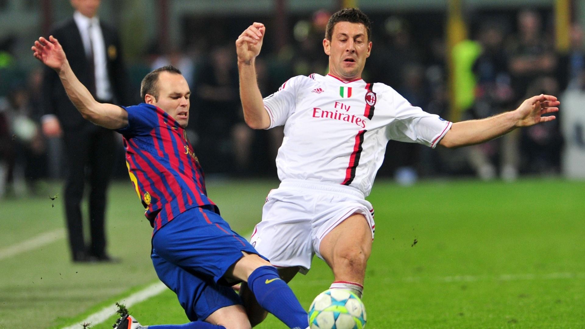 Bonera, do Milan, e Iniesta, do Barcelona, disputam a bola em partida pela Liga dos Campeões