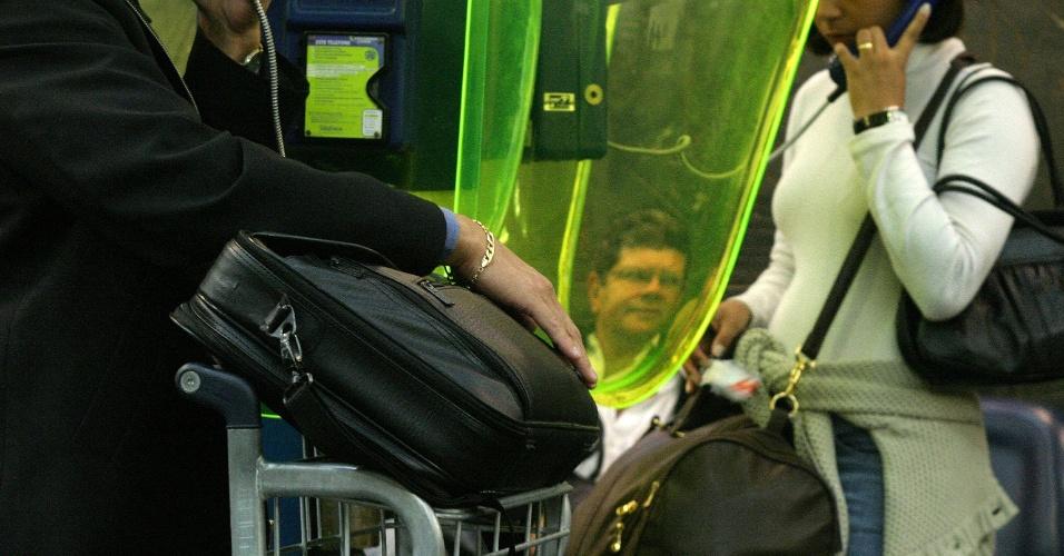 Homem segura maleta com laptop enquanto conversa ao telefone no aeroporto de Congonhas, na zona sul de São Paulo