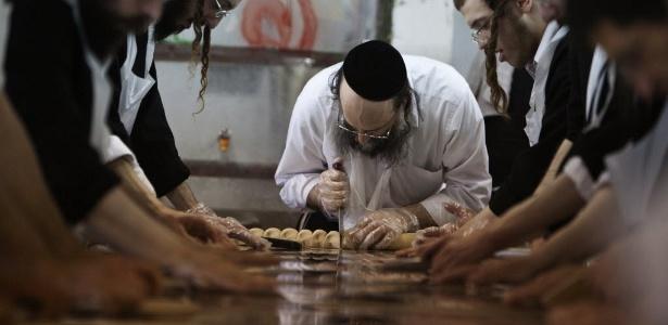 Judeus ultraortodoxos preparam o matzá, pão sem fermento para ser comido na Páscoa judaica