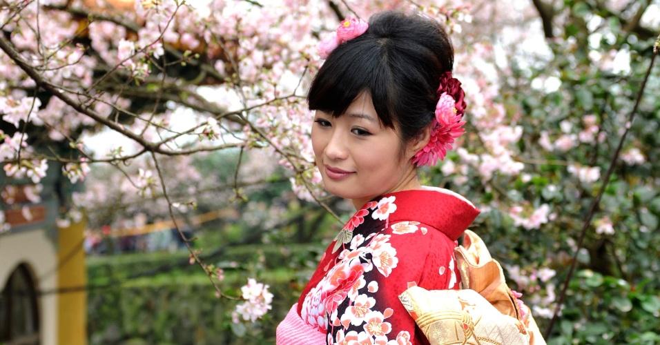 Mulher com os trajes tradicionais posa para fotos sob cerejeira em um templo taoísta, em Taipei (Taiwan)