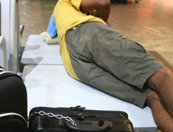 Passageiro acorrenta bagagem para dormir sem medo de roubo, no aeroporto de Guarulhos, em São Paulo