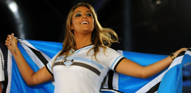 Ex-BBB Monique sorri e exibe a bandeira do Grêmio durante o lançamento dos novos uniformes; a torcedora ilustre vestiu uma camisa retrô da coleção