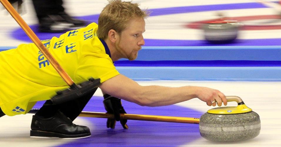 Atleta lança sua pedra durante jogo de Curling no Campeonato Mundial em Basel