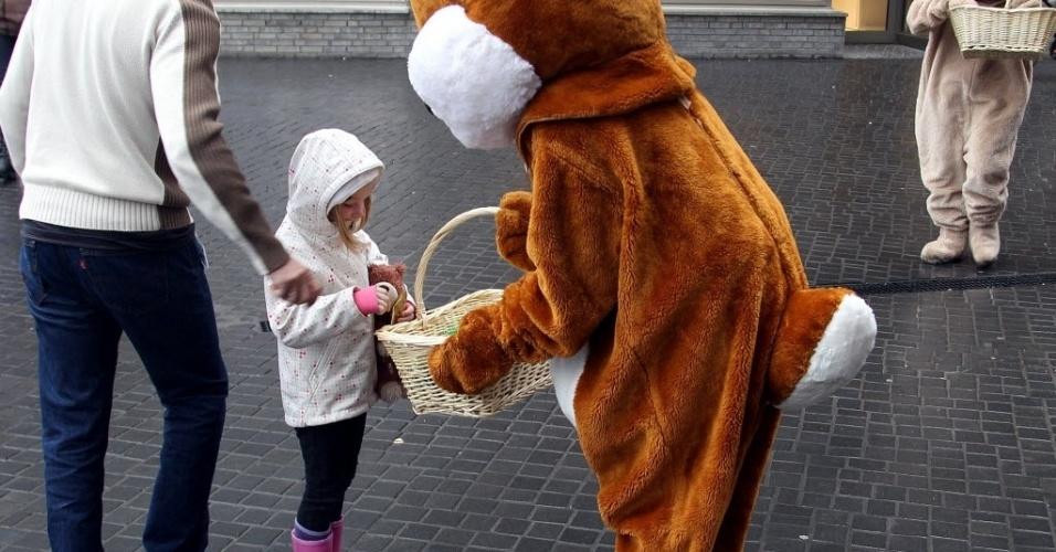 Fantasiado de Coelho da Páscoa distribui doces a crianças em Berlim (Alemanha), que nesta quarta-feira (4) registra temperaturas em torno de 4ºC