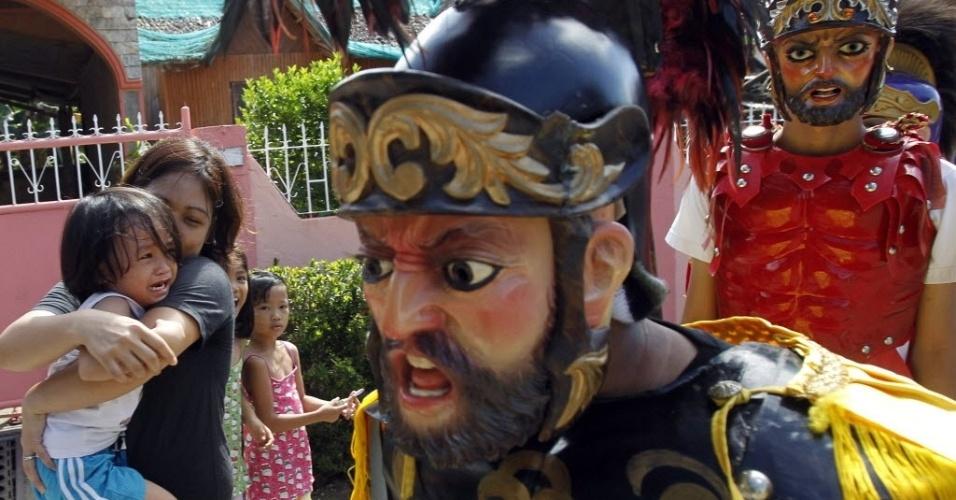 Garota chora ao ver penitente fantasiado de centurião romano na cidade de Mogpog durante o Lenten, ritual católico celebrado anualmente nas Filipinas