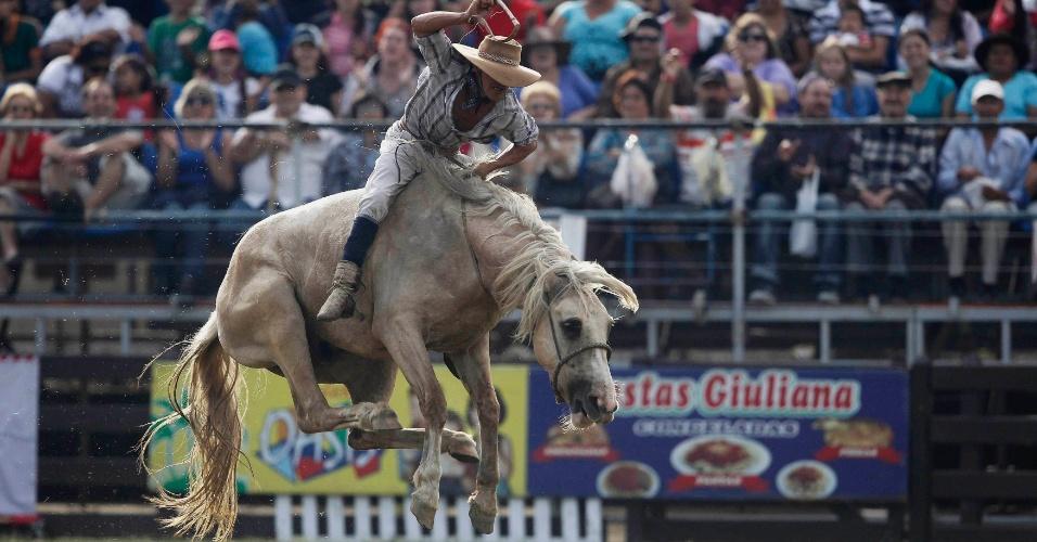 """Gaucho (vaqueiro) monta um cavalo bravo durante a celebração da Semana """"Criolla"""" em Montevidéu"""