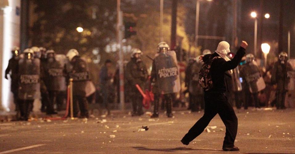 Manifestante joga pedra contra policiais em Atenas, na Grécia, durante protesto