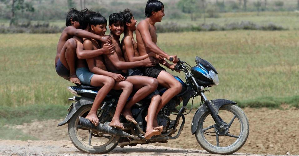 Meninos montam em uma moto na aldeia Chachura, em Uttar Pradesh