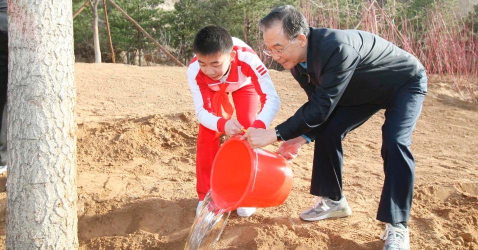 O premiê chinês, Wen Jibao (direita), rega muda ao lado de estudante em evento para incentivar o plantio voluntário de árvores em Pequim, na China
