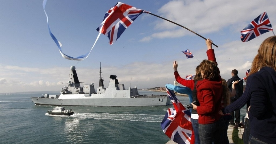 """Parentes e amigos acenam à tripulação do destróier da Marinha britânica HMS Dauntless, que zarpou nesta quarta-feira (4) rumo ao Atlântico Sul para uma missão de seis meses que inclui o patrulhamento das Ilhas Malvinas. Recentemente, cujo envio levou o governo argentino a denunciar uma """"militarização do conflito"""" por parte do Reino Unido em meio a uma escalada verbal entre os dois países pela soberania das ilas Malvinas (Falklands para os ingleses)."""