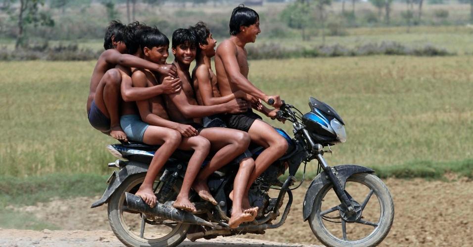 Seis crianças voltam para casa em uma mesma moto depois de se banharem em um canal em Chachura, na Índia