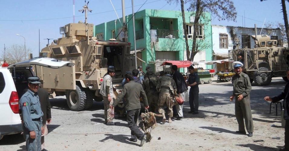 Soldados da Isaf, a força da Otan no Afeganistão, socorrem homem ferido e inspecionam local em que um atentado suicida, na cidade de Maymana, deixou ao menos quatro policiais e seis civis mortos e dezenas de feridos