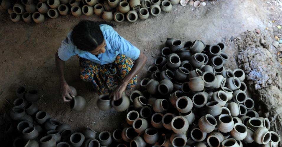Vendedora exibe panelas de barro em Colombo, no Sri Lanka