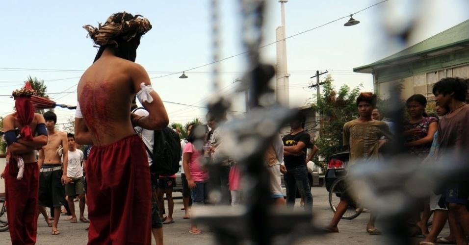 Crucifixos são vistos perto de pessoas que praticam penitência com autoflagelação às vésperas da Sexta-feira Santa, em frente a igreja da cidade de São Fernando, na província de Pampanga, em Manila