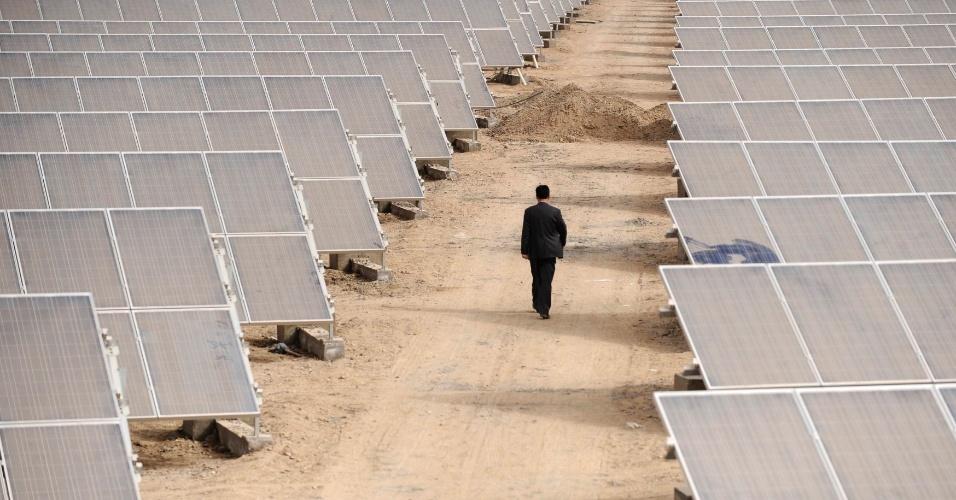 Homem caminha em meio a painéis de energia solar em Aksu, na região autônoma de Xinjiang Uyghur, na China
