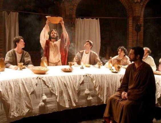 Jesus (José Barbosa) entre os apóstolos na Última Ceia com Judas (Caco Ciocler) em primeiro plano durante a apresentação de Nova Jerusalém