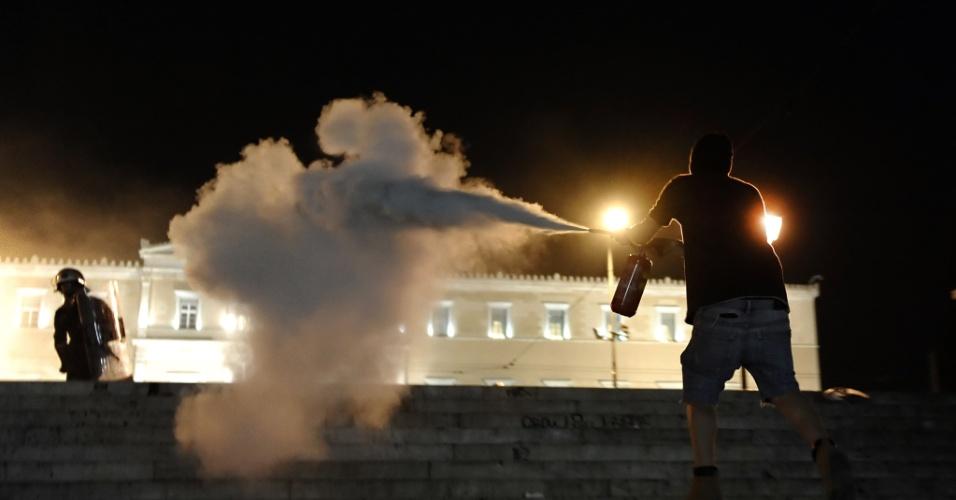Manifestante enfrenta a polícia em Atenas, na Grécia, após um aposentado grego de 77 anos se suicidar na frente do Parlamento do país devido às dificuldades econômicas que atravessava