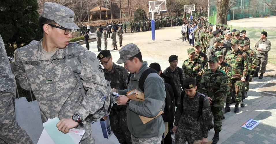 Soldados sul-coreanos fora de seu colégio eleitoral esperam em fila em Seul, na Coreia do Sul, para votar antecipadamente para as eleições parlamentares da próxima semana