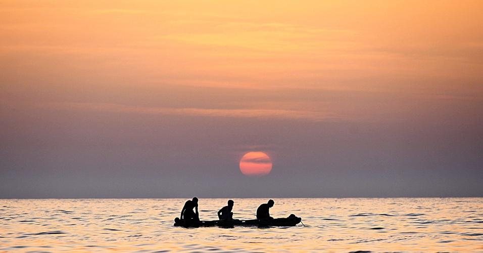 Pescadores palestinos trabalham sob o pôr-do-sol, na Faixa de Gaza