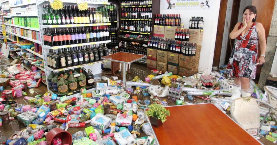 Comerciantes arrumam os estragos provocados pela chuva em Teresópolis (RJ), que deixou pelo menos cinco mortos na madrugada de sábado (7)