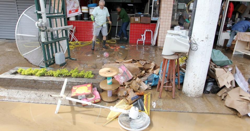 Moradores e comerciantes arrumam os estragos provocados pela chuva em Teresópolis (RJ), que deixou pelo menos cinco mortos na madrugada de sábado (7)