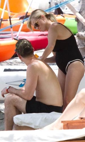"""De férias na Costa Rica com a família, Reese Witherspoon exibe """"barriguinha"""" de grávida enquanto passa protetor solar no marido, Jim Toth (4/4/12)"""