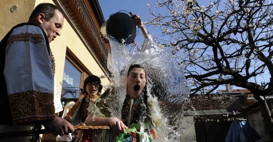 Jovens vestindo roupas tradicionais jogam balde d'água em garota nas comemorações da Páscoa na Eslováquia. É costume no país molhar e chicotear garotas, o que se crê assegurar sua fertilidade e beleza